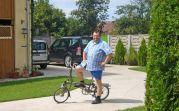 Herbert Hubert mit Klappfahrrad im Heimathaus. Dorf und Umgebung lassen sich mit dem Rad gut erkunden. Fahrräder zum Ausleihen gibt es auch vor Ort. Foto: Roswitha Csonti